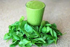 Green smoothie with spinach around it