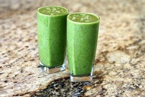 Two green smoothies on a bench