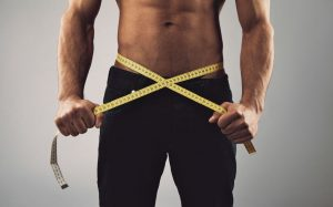 Fitness man measuring his body. Cropped and mid-section image of young man measuring his waist with tape measure against grey background. Health and fitness concept.
