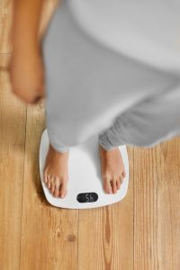 Diet. Top View Of Female Bare Feet Standing On A Scale. Caucasian Young Woman Measuring Body Weight On Weighing Scale At Home. Weight Loss. Dieting; Exercising. Healthy Eating; Lifestyle.