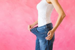 Woman showing her old big jeans after successful weight loss diet