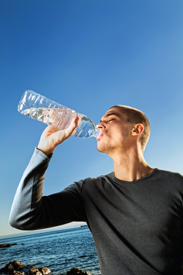 Man-drinking-water-from-a-plastic-water-bottle-near-the-beach