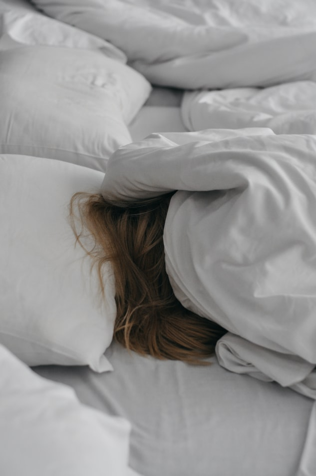 Person-sleeping-in-bed-with-covers-over-head