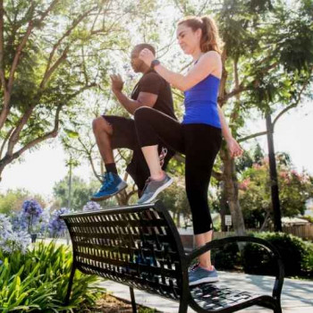 Couple doing step ups on park bench