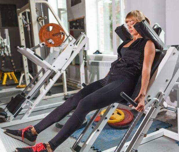 Woman on hack squat machine