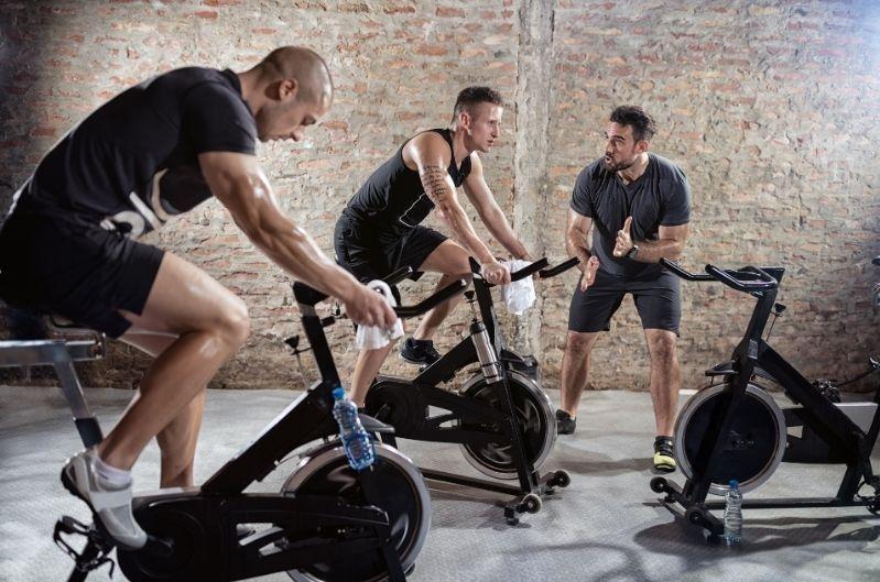 two men on spin bikes doing cardio