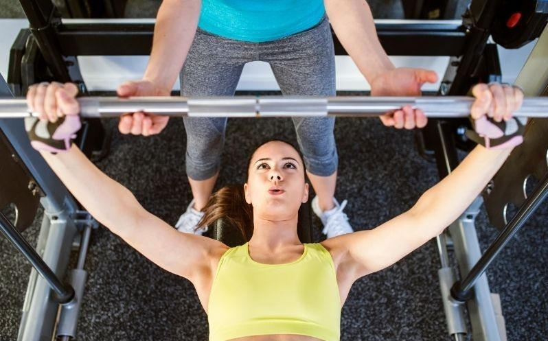 woman benching with a spotter