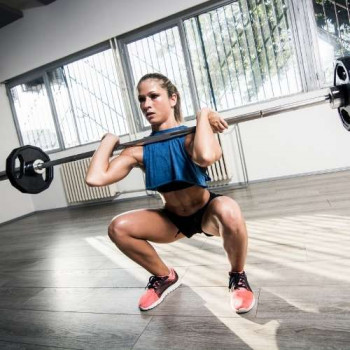 woman doing front squats with barbell